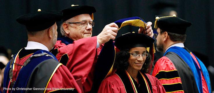A professor hooding a PhD graduate.